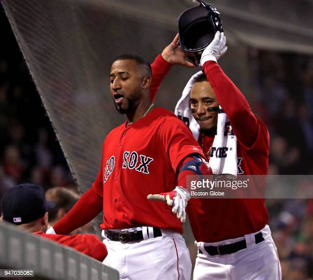 Boston Red Sox second baseman Eduardo Nunez is ready for a dugout celebration as Boston Red Sox right fielder Mookie Betts removes his helmet in the...