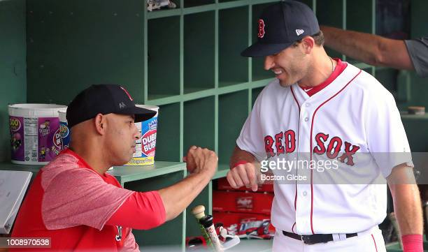 Boston Red Sox second baseman Ian Kinsler right gets a fist bump from manager Alex Cora as he comes into the dugout just before the start of the game...