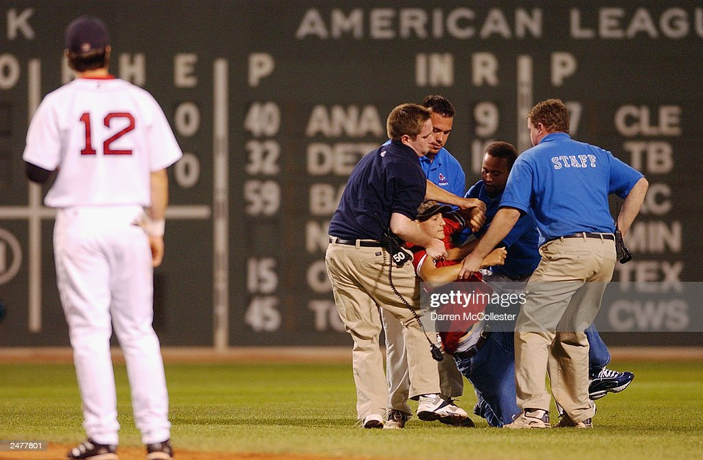 Boston Red Sox second baseman Todd Walker #12 watches as a fan is taken away after running onto the field during the game against the Seattle Mariners at Fenway Park August 24, 2003 in Boston, Massachusetts. The Red Sox won 6-1, further tightening the race in the American League east.