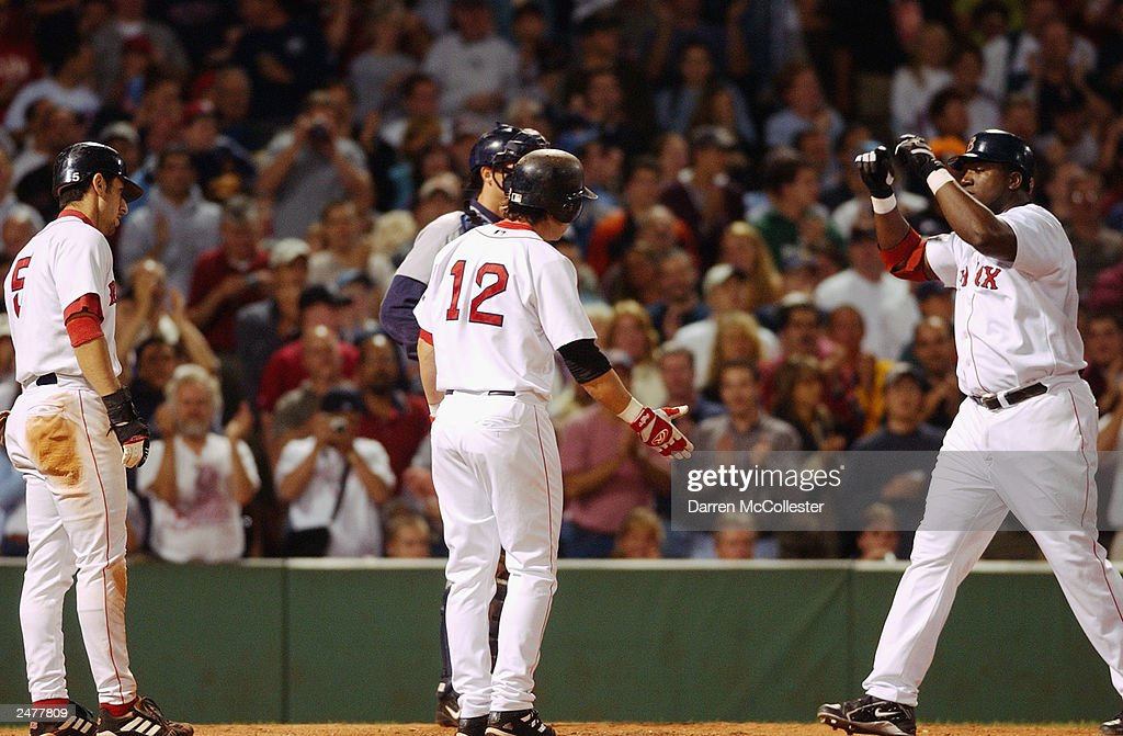 Boston Red Sox shortstop Nomar Garciaparra #5 and second baseman Todd Walker #12 congratulate DH David Ortiz #34 after a 4th inning 3 run blast during the game against the Seattle Mariners at Fenway Park in Boston, Massachusetts. The Red Sox won 6-1, further tightening the race in the American League east.
