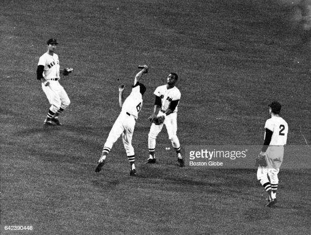 Boston Red Sox shortstop Rico Petrocelli makes a catch with teammates Carl Yastrzemski Reggie Smith and Mike Andrews surrounds him in the fifth...