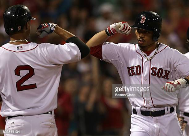 Boston Red Sox shortstop Xander Bogaerts greets Boston Red Sox center fielder Mookie Betts with an elbow bump after Betts' solo home run in the...