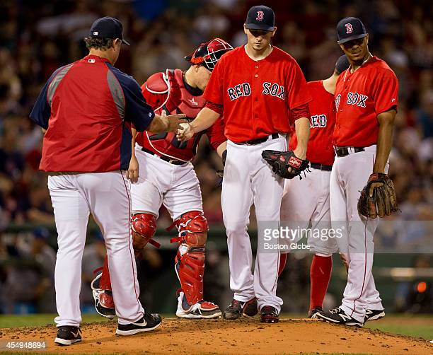 Boston Red Sox starting pitcher Allen Webster handing off the ball to manager John Farrell during sixth inning action against the Toronto Blue Jays...