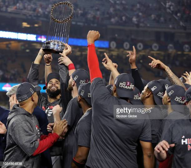 Boston Red Sox starting pitcher David Price hoists the trophy as the Red Sox celebrate their World Series championship win The Los Angeles Dodgers...