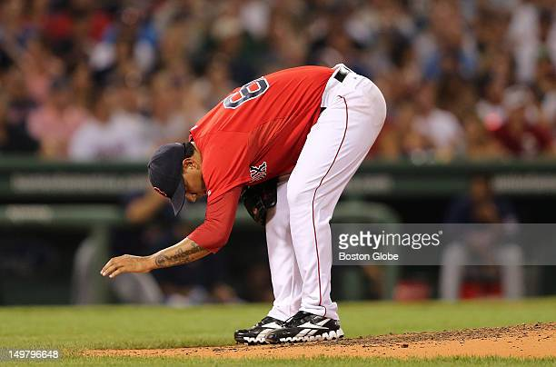 Boston Red Sox starting pitcher Felix Doubront wipes dirt off the mound after throwing another ball during the fifth inning as the Boston Red Sox...