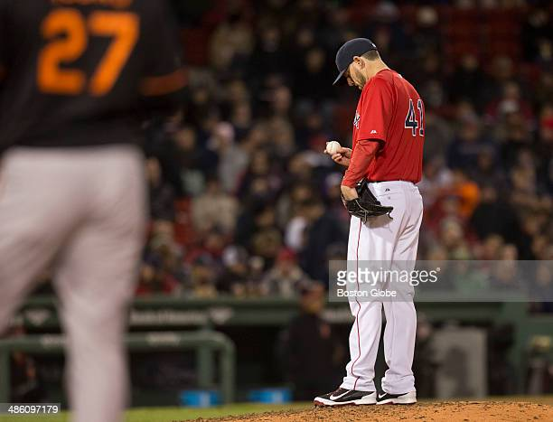 Boston Red Sox starting pitcher John Lackey looks down at the ball after giving up a walk to Baltimore Orioles player Delmon Young as manager John...