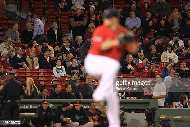 Boston Red Sox starting pitcher Jon Lester warms up during the first inning with many empty seats in background as the Boston Red Sox took on the...