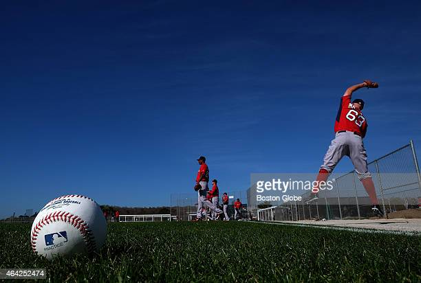 Boston Red Sox starting pitcher Justin Masterson at foreground far right leaps for an errant high throw as he joined fellow Red Sox pitchers for long...