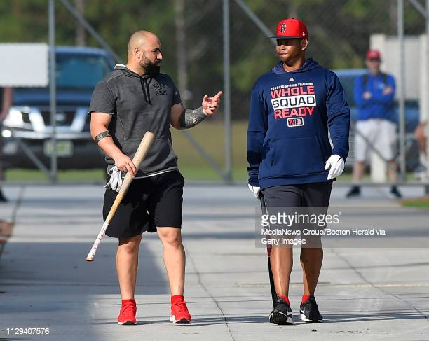 Boston Red Sox teammates Sandy Leon left and Rafael Devers talk after taking batting practice during a spring training workout in Fort Myers Florida...