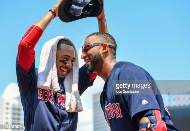 Boston Red Sox third baseman Eduardo Nunez has his helmet removed by right fielder Mookie Betts after his fifth inning two run home run during the...