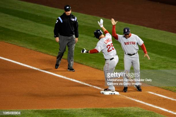 Boston Red Sox third baseman Mike Lowell is greeted at first base by coach Luis Alicea after hitting a solo homerun off Colorado Rockies pitcher...