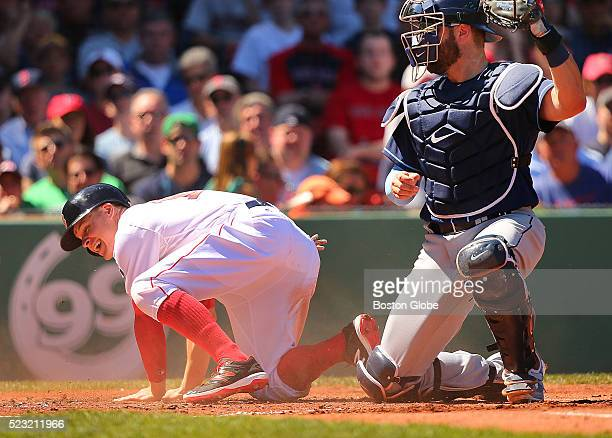 Boston Red Sox utility player Brock Holt is out at home plate on a tag by Tampa Bay Rays catcher Curt Casali during the first inning at Fenway Park...