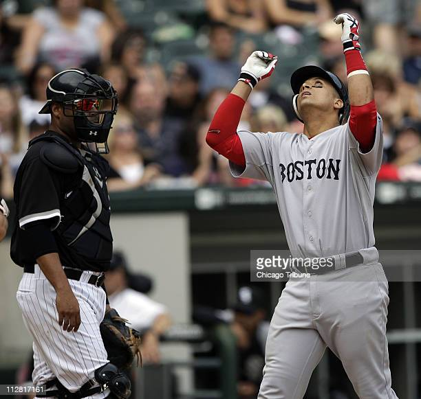 Boston Red Sox Victor Martinez crosses home plate after hitting a three-run homer in the ninth inning as Chicago White Sox catcher Ramon Castro looks...