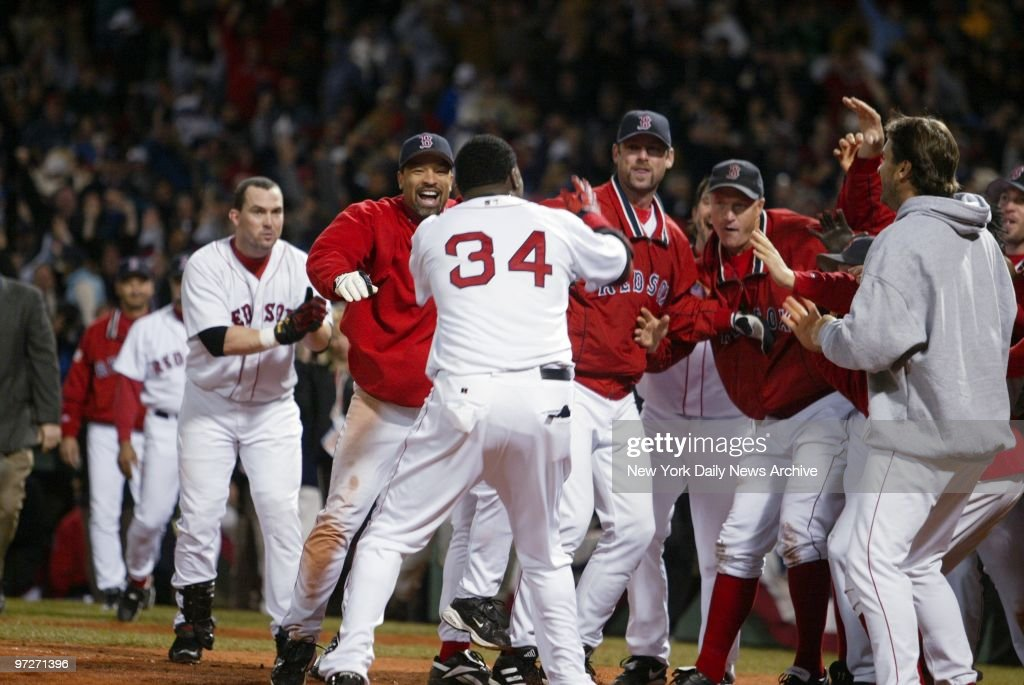 Boston Red Sox's David Ortiz (34) is greeted at the plate by teammates after hitting a game-winning, two-run homer in the 12th inning of the American League Championship Series at Fenway Park to beat the New York Yankees, 6-4, and stave off elimination.