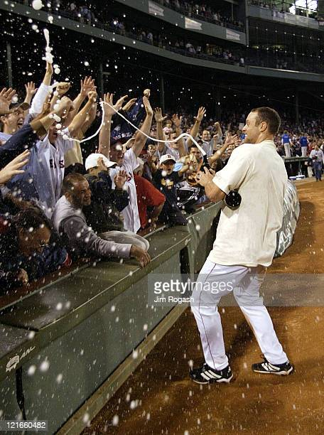 Boston Red Sox's Gabe Kapler sprays the crowd with bubbly in celebration after the Red Sox clinched a playoff spot in the American League after...