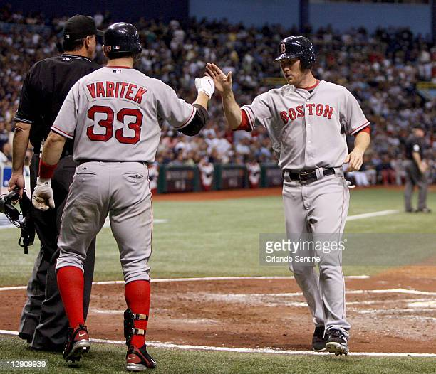 Boston Red Sox's Jason Varitek congratulates Jason Bay who scored on a sacrifice fly by Jed Lowrie in the fifth inning against the Tampa Bay Rays...