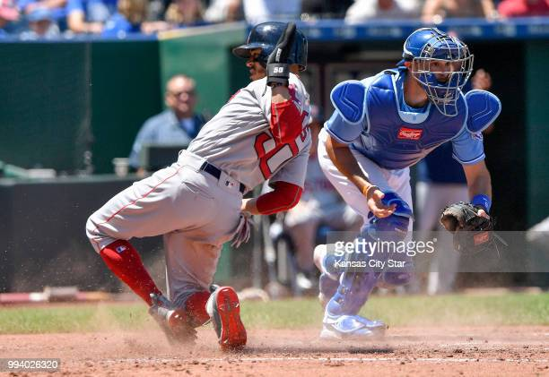 Boston Red Sox's Mookie Betts scores before the tag from Kansas City Royals catcher Drew Butera on a sacrifice fly by Steve Pearce in the third...