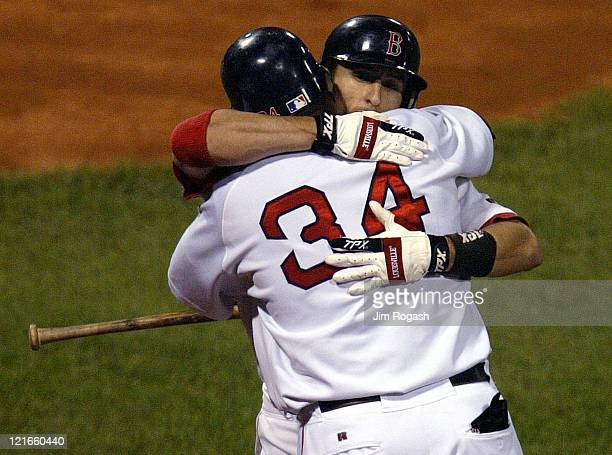 Boston Red Sox's Nomar Garciaparra is hugged by teammate David Ortiz after Garciaparra hit a home run that helped the Red Sox to clinched a playoff...