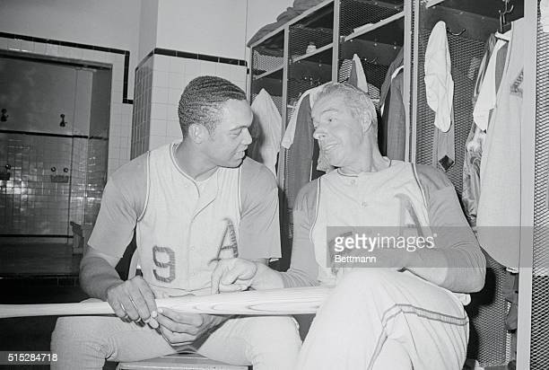 Reggie Jackson and Joe Dimaggio coach of the Oakland Athletics enjoy a light moment as Dimaggio gives some pointers to the leagueleading slugger in...