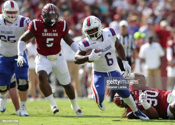 Boston Scott of the Louisiana Tech Bulldogs runs away from Taylor Stallworth of the South Carolina Gamecocks during their game at WilliamsBrice...