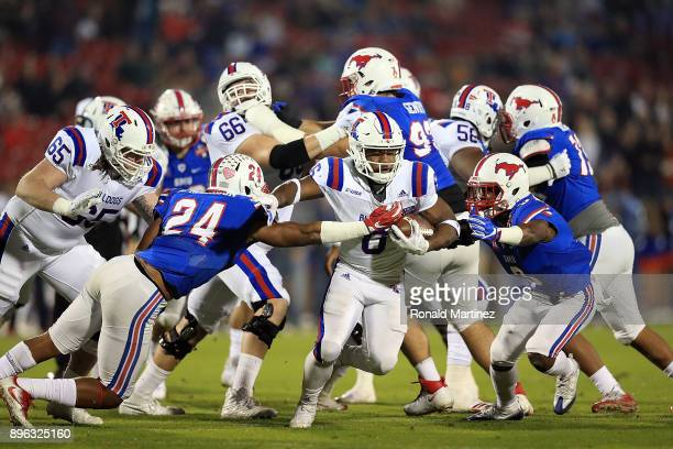 Boston Scott of the Louisiana Tech Bulldogs runs the ball against Delano Robinson and Cedric Lancaster of the Southern Methodist Mustangs in the...