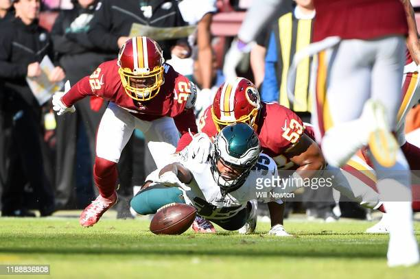 Boston Scott of the Philadelphia Eagles and Jon Bostic of the Washington Redskins dive after a fumble during the first half at FedExField on December...