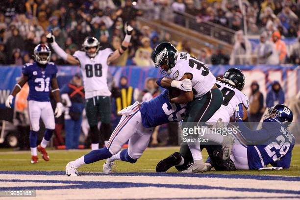 Boston Scott of the Philadelphia Eagles scored a touchdown against Lorenzo Carter of the New York Giants during the third quarter in the game at...