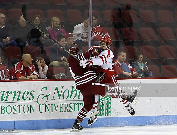 Boston University forward Bobo Carpenter checks UMass Amherst forward Austin Plevy during first period action of the Hockey East Tournament at the...