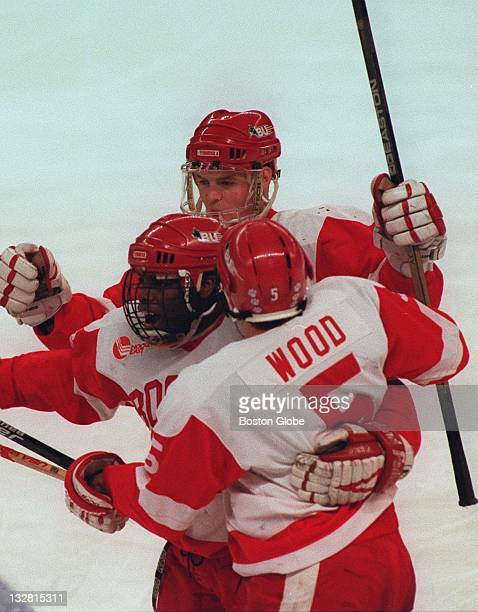 Boston University men's ice hockey players Doug Wood right Mike Grier left and Chris Kelleher above celebrate after BU's second goal against Maine at...
