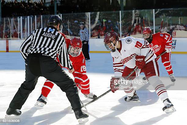 Boston University Terriers forward Clayon Keller and UMass Minutemen forward Jack Suter take a face off during a Frozen Fenway NCAA Men's Division 1...