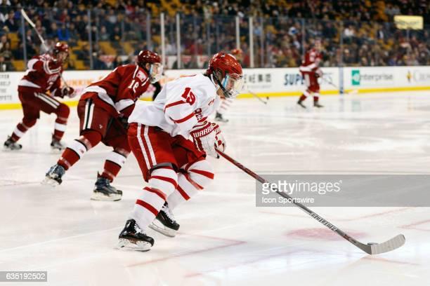 Boston University Terriers forward Clayton Keller clears the puck past Harvard University Crimson defenseman Adam Fox during the second period of the...