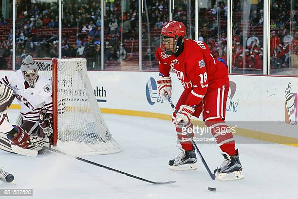 Boston University Terriers forward Jordan Greenway holds the puck down low on the power play watched by UMass Minutemen goaltender Ryan Wischow...