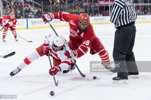 Boston University Terriers forward Jordan Greenway shoves Cornell Big Red forward Kyle Betts for the puck during a faceoff in the third period of the...