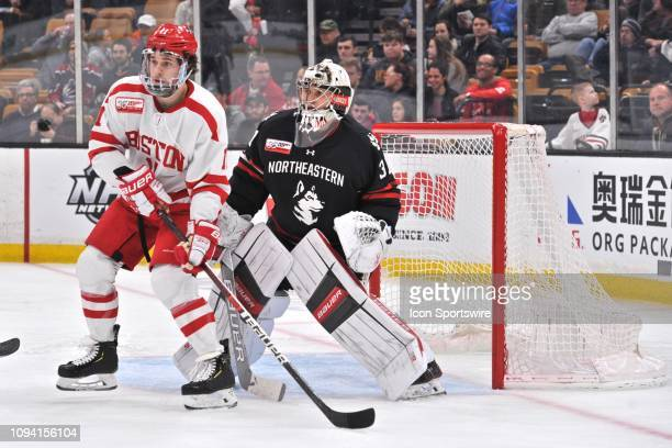 Boston University Terriers forward Patrick Curry takes up a position in front of Northeastern Huskies goaltender Cayden Primeau . During the Boston...