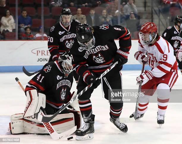 Boston University's Kieffer Bellows puts pressure on Northeastern University goalie Ryan Ruck as Adam Gaudette clears the puck during the first...