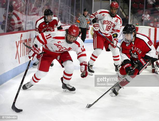 Boston University's Patrick Curry controls the puck in front of Northeastern University's Adam Gaudette during the first period Boston University...