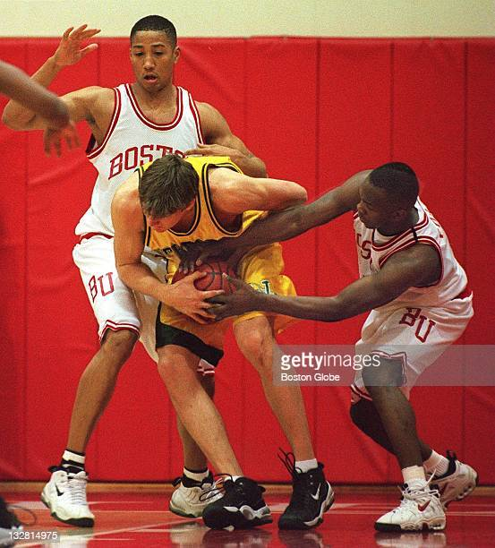 Boston University's Walter Brown covers University of Vermont's Erik Nelson as Boston University's LeVar Folk grabs the ball during Sunday's game at...