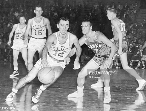 Boston's Bob Cousy tries to dribble past the guard of Milwaukee's Bob Harrison during the third period of their game at the Garden tonight Boston...