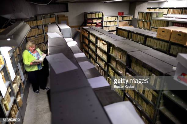 Boston's Register Patricia A McMahon looks through Boston birth certificate books dating from the 1950's which are stored in the dungeon as she calls...