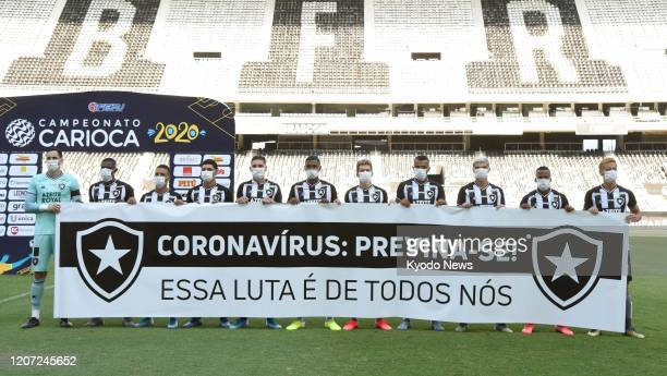 Botafogo players wearing face masks pose for a group photo ahead of a Rio de Janeiro state championship match against Bangu on March 15 2020 The...