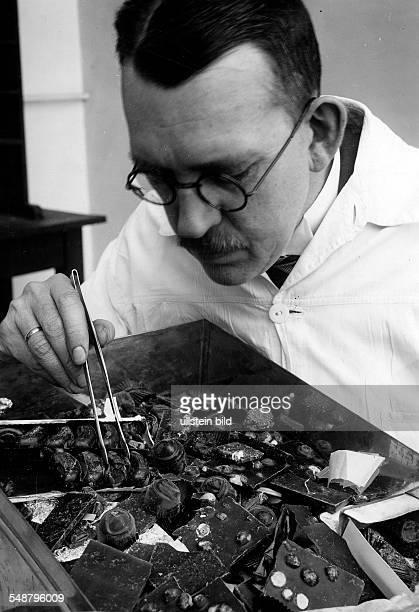 Botanist Germany *18841961 The director of the 'Gesellschaft fuer Vorratsschutz in Berlin' examining chocolates ca 1935 Photographer Walter Gircke...