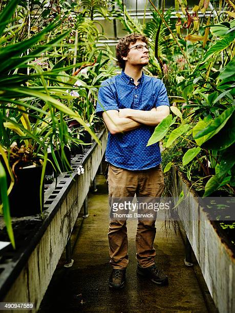 Botanist in research greenhouse looking at plants