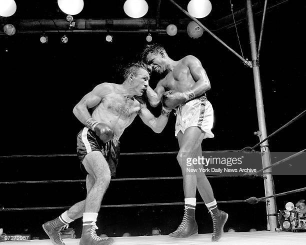 Both Carmen Basilio and Ray Robinson grimace as they exchange brusing belts in 13th Crowd of 38000 witnessed thrilling bout
