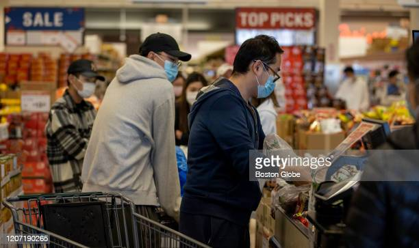 Both customers and cashiers wear face masks at 99 Ranch Market in Quincy, MA on March 13 soon after President Trump declared a national emergency...