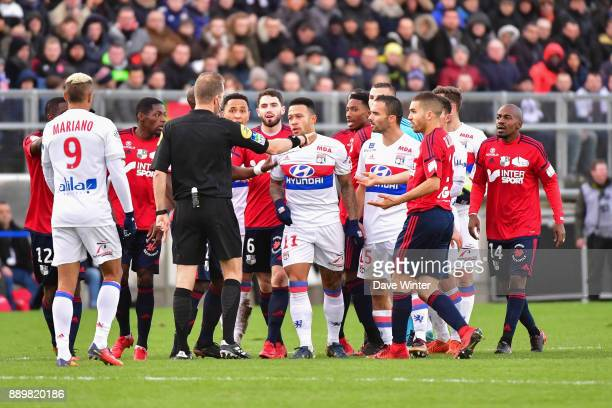 Both sets of players contest a decision by referee Olivier Thual during the Ligue 1 match between Amiens SC and Olympique Lyonnais at Stade de la...