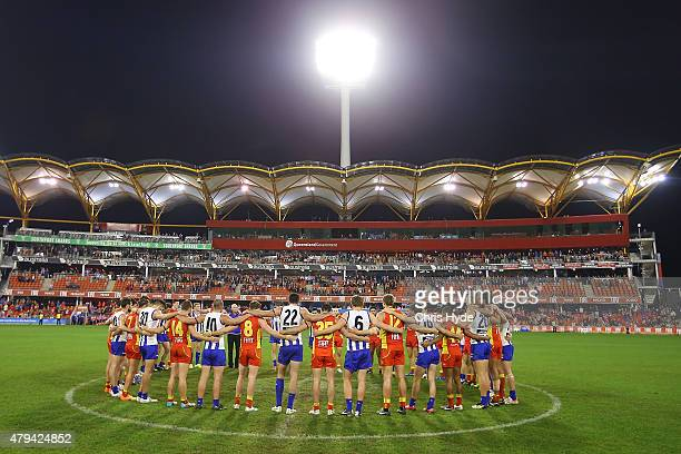 Both sides huddle in the middle of the ground to pay respect to Phil Walsh during the round 14 AFL match between the Gold Coast Suns and the North...