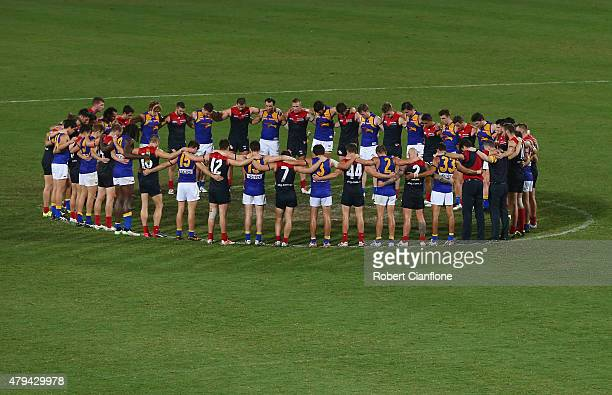 Both sides huddled together in the middle of the ground after the game, to pay respect to Phil Walsh after the round 14 AFL match between the...