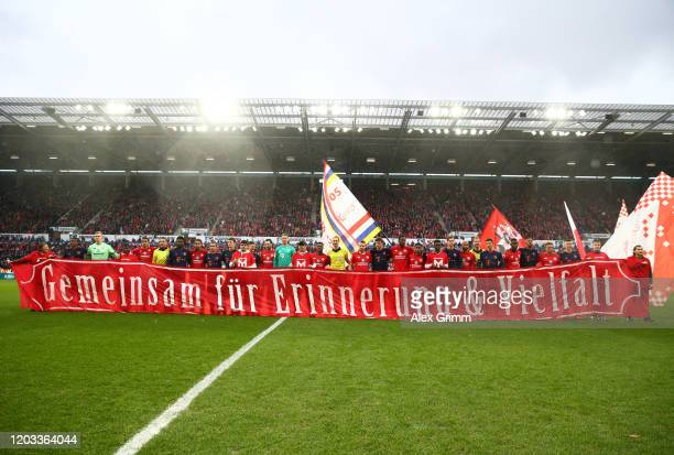 Both sides line up before kickoff with a banner to commemorate 75th anniversary of the liberation of Auschwitz concentration camp during the...