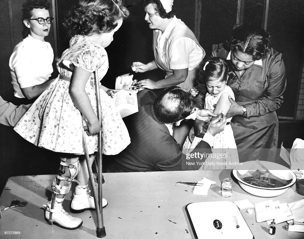 Both Sides of the Story. Joanne Wilson, 1955 National March of Dimes Poster Girl, looks on as her friend Roslyn Feigenbaum, gets a Salk antipolio shot in P.S. 104, Far Rockaway, Queens. Yesterday, more than 22,000 school children were inoculated against polio. However, about 29% of children failed to show up.