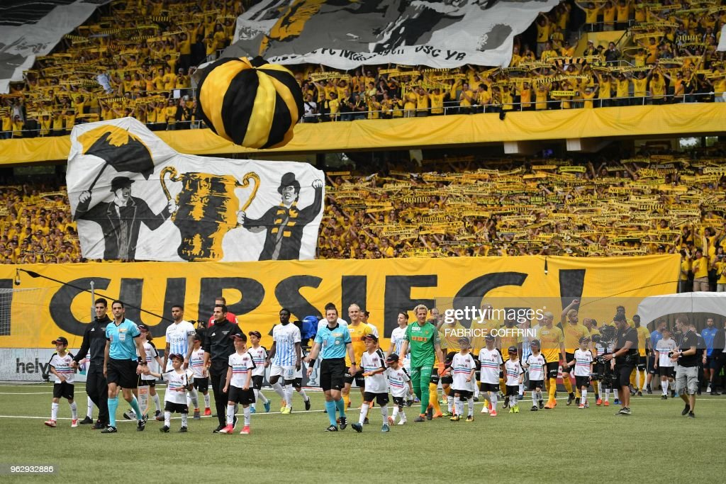 Both teams enter the football pitch as they are greeted by supporters prior to the Swiss Football Cup final match between FC Zurich and BSC Young Boys at the Stade de Suisse stadium, on May 27, 2018 in Bern.
